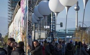 Des personnes regardent une oeuvre lumineuse installée le long de l'ancien Mur de Berlin, le 8 novembre 2014