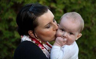 Une maman embrasse son bébé.