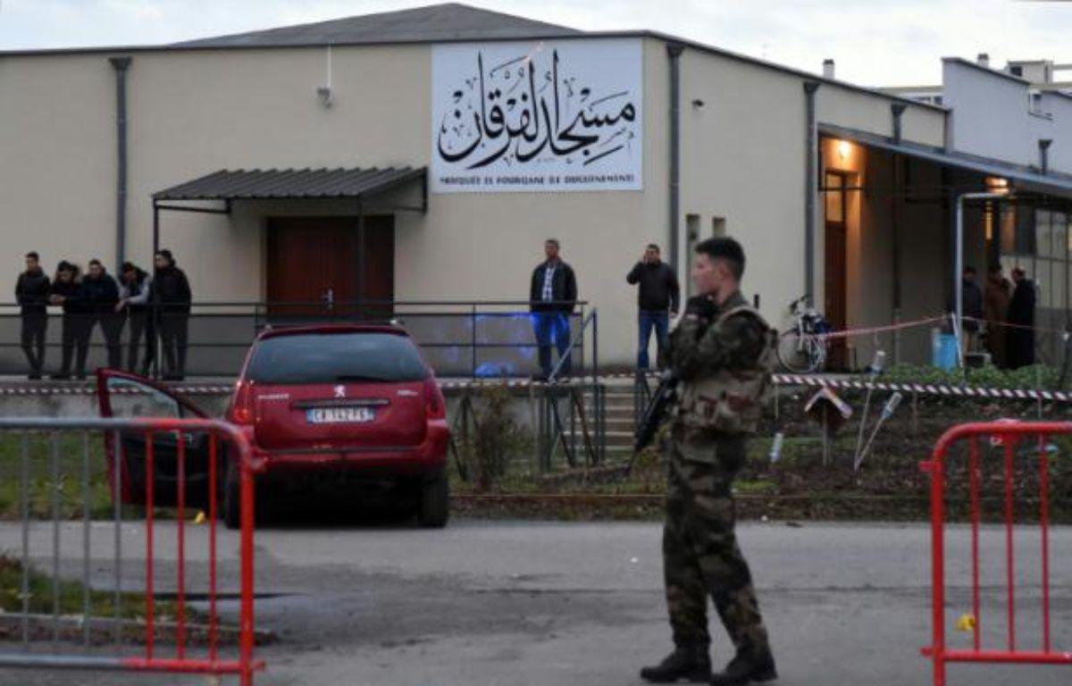 Des policiers près d'une voiture endommagée devant la mosquée de Valence, le 1er janvier 2016, après qu'un homme a foncé en voiture sur un militaire – PATRICK GARDIN AFP