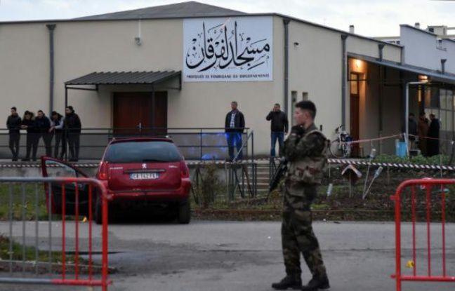 Des policiers près d'une voiture endommagée devant la mosquée de Valence, le 1er janvier 2016, après qu'un homme a foncé en voiture sur un militaire