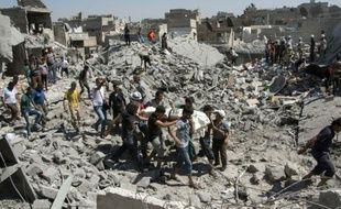 Des personnes transportent un corps après des frappes de l'armée de l'air du régime syrien, le 21 septembre 2015 à Alep