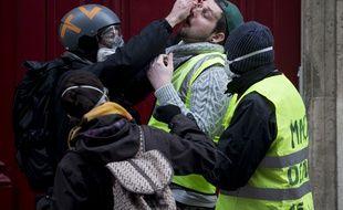 """Des """"gilets jaunes"""" aident l'un des leurs après un tir de gaz lacrymogène, le 8 décembre 2018 à Paris."""