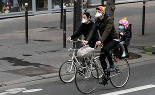 Coronavirus: Une famille avec des masques en vélo.
