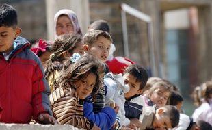 Sidon (Liban), le 22 mars 2015. Des enfants syriens attendant dans un camp de réfugiés au Liban.