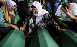 Des personnes pleurent des proches parmi les 136 cercueils de victimes du massacre de Srebrenica qui attendaient, le 9 juillet 2015, d'être enterrés dans le mémorial de cette ville