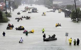 Rescue boats fill a flooded street at flood victims are evacuated as floodwaters from Tropical Storm Harvey rise Monday, Aug. 28, 2017, in Houston. (AP Photo/David J. Phillip)/TXDP401/17240749664716/1708282347