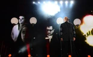 British singer Peter Gabriel performs during a Street Party organized by German governement to mark the 25th anniversary of the fall of the Berlin Wall, in front of the Brandenburg Gate on November 9, 2014 in Berlin.  AFP PHOTO / JOHN MACDOUGALL