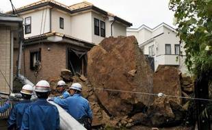 Une maison et un poteau électrique endommagés par une chute de pierres lors du passage du typhon Wipha, le 16 octobre 2013 à Kamakura, dans la banlieue de Tokyo