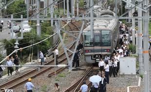 Les passagers d'un train ont dû rejoindre la gare à pied après le tremblement de terre à Osaka, le 18 juin 2018.