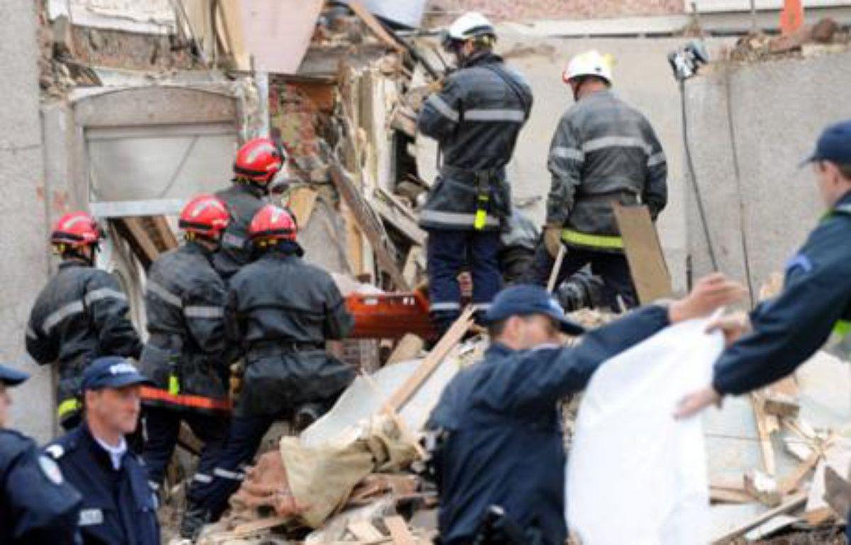 Les pompiers extraient le corps d'un adjoint au maire d'Hautmont, l'une des quatre victimes de la mini-tornade, qui a dévasté tout un quartier de la ville hier soir.  – AFP PHOTO / François Lo Presti