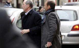 L'ex-ministre de l'Intérieur Claude Guéant est escorté par la police pour être présenté à un juge à Paris le 7 mars 2015