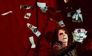 Le chanteur Alice Cooper jette en l'air des faux billets de 100 dollars lors d'un show dans le Michigan, le 2 juillet 2014.