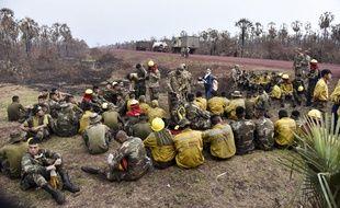 Des soldats boliviens se reposent après avoir combattu le feu dans le parc national Otuquis, le 26 juin 2019.