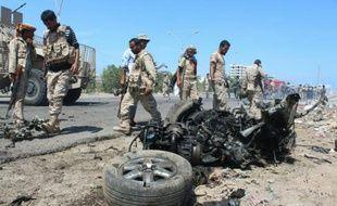 Les forces de sécurité yéménites inspectent le lieu de l'explosion d'une voiture piégée à Aden le 1er mai 2016