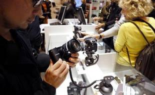 Un visiteur du Salon de la photo à Paris manipule un appareil, le 8 novembre 2012