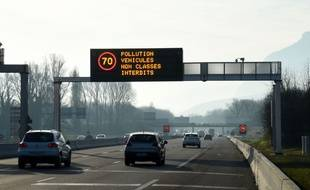 (FILES) This file photo taken on December 13, 2016 shows vehicles driving on a highway while a board displays traffic reduction measures, near the city of Grenoble, eastern France. The traffic restrictions in Grenoble were renewed on December 17, 2016 for the 8th day in a row, while the pollution now extends to five geographical basins, from the Rhone Valley to the Arve Valley. / AFP PHOTO / JEAN-PIERRE CLATOT