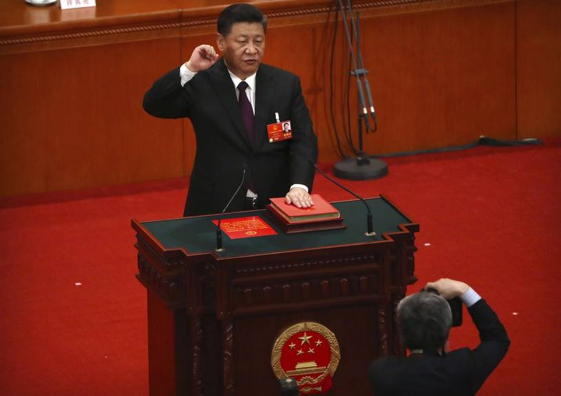 Chinese President Xi Jinping takes the oath of office after being formally reelected to a second term as China's President during a plenary session of China's National People's Congress (NPC) in Beijing, Saturday, March 17, 2018. Xi was reappointed Saturday as China's president with no limit on the number of terms he can serve. The ceremonial National People's Congress voted unanimously for Xi's second five-year term as president. (AP Photo/Mark Schiefelbein)/XMAS101/18076132434443/1803170449