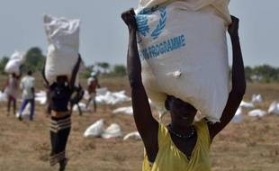 Des villageois portent le 23 février 2015 des sacs de nourriture parachutés par le Programme alimentaire mondial (PAM) près de leur village à Nyal, en Soudan du Sud, près de la frontière avec le Soudan