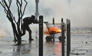 Un manifestant pousse un chariot face aux forces de l'ordre à Nantes, durant la manifestation contre l'aéroport Notre-Dame-des-Landes, le 22 février 2014.