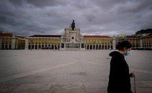 Une passante traverse la Praça do Comércio à Lisbonne.