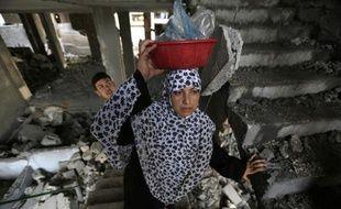 Une femme palestinienne se rend dans sa maison détruite après une frappe israélienne, le 13 juillet 2014 à Gaza