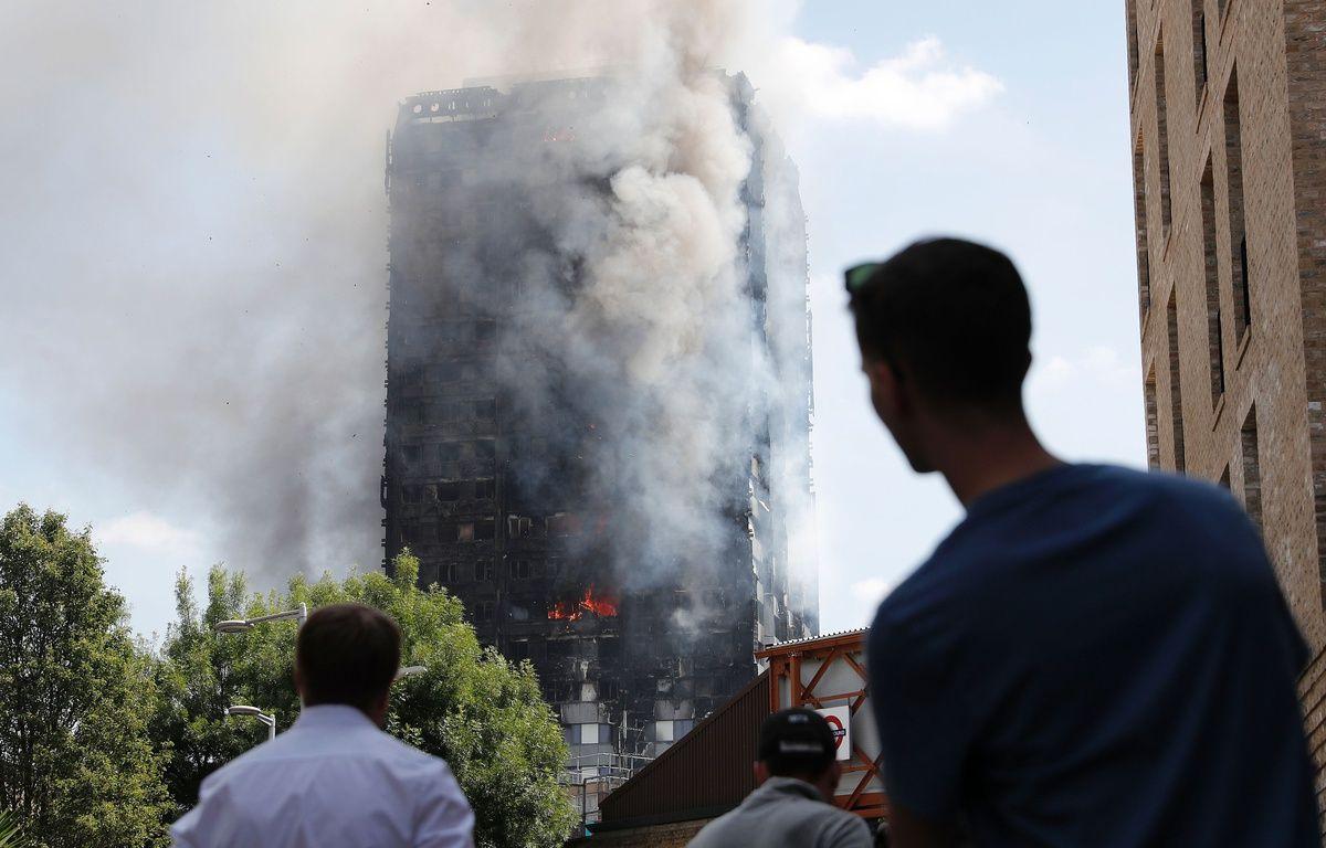 Des passants constatent l'état de la Grenfell Tower après l'incendie qui l'a ravagée dans la nuit de mardi à mercredi. – AFP