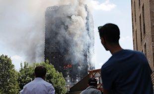 Des passants constatent l'état de la Grenfell Tower après l'incendie qui l'a ravagée dans la nuit de mardi à mercredi.