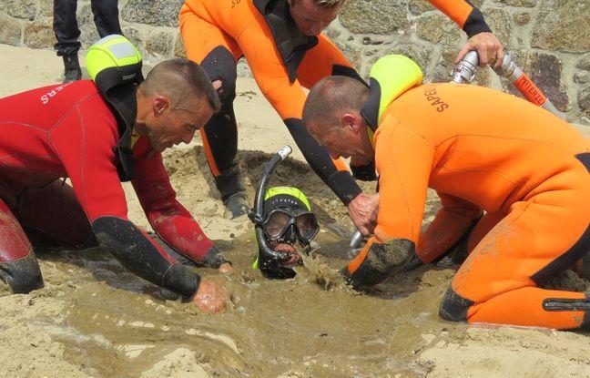 Les pompiers ont placé un masque et un tuba sur la victime et commencent à arroser tout autour avec la lance de désensablement.