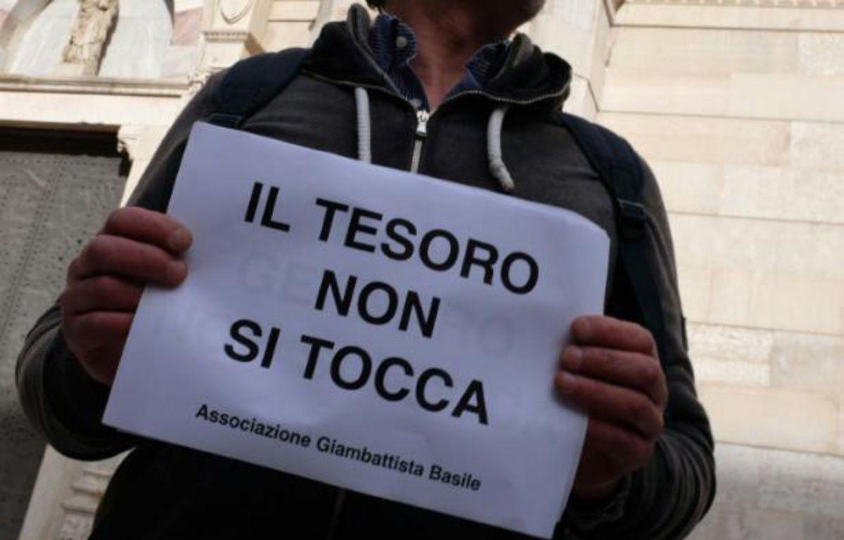 """Une affiche """"ne pas toucher au trésor"""" est brandie lors d'une manifestation, le 5 mars 2016 à Naples, pour protester contre la prise de contrôle par l'Eglise catholique du trésor de San Gennaro – Mario LAPORTA AFP"""