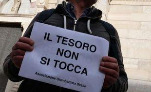 """Une affiche """"ne pas toucher au trésor"""" est brandie lors d'une manifestation, le 5 mars 2016 à Naples, pour protester contre la prise de contrôle par l'Eglise catholique du trésor de San Gennaro"""