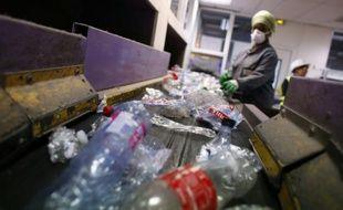 Un salarié trie les déchets plastiques à Sevran le 27 août 2015