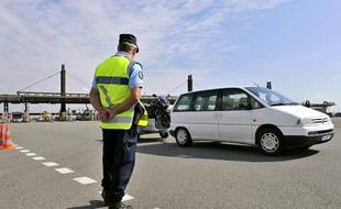Un gendarme contrôle des véhicules, le 13 août 2010 au péage autoroutier  de Gerzat dans le cadre du dispositif de sécurisation routière mis en  place par la gendarmerie.