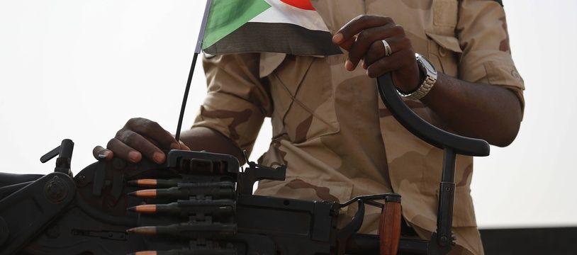 Un militaire soudanais avec un drapeau du Soudan sur son arme (illustration).