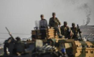 La ville syrienne de Kobané, au loin, alors que l'armée turque prend position, dans la ville de Suruc, à la frontière avec la Syrie, le 3 octobre 2014