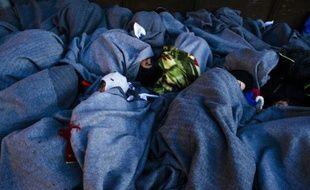Des migrants endormis sous des couvertures sur le rivage de l'île de Lesbos le 15 octobre 2015 en provenance de Turquie