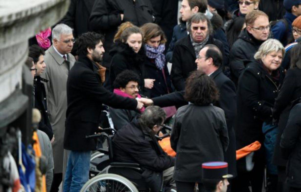 François Hollande avec des victimes et des familles de victimes des attentats, lors d'une cérémonie place de la République le 10 janvier 206 à Paris – DOMINIQUE FAGET AFP