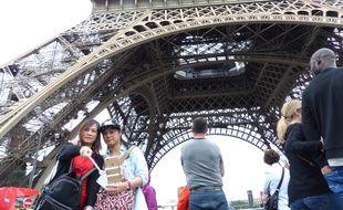 Deux touristes asiatiques immortalisent leur passage sous la tour Eiffel le 12 juillet 2016.