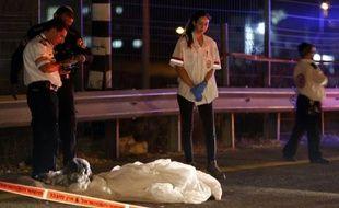 Des membres des forces de la sécurité israélienne et des secouristes devant le corps d'un palestinien abattu alors qu'il tentait de poignardé un israélien dans une station-service de Cisjordanie occupée, sur l'autoroute 443 au sud-ouest de Ramallah, le 9 août 2015