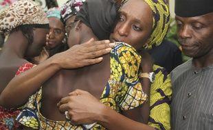 L'épouse du vice-président nigérian réconforte les lycéennes libérées par Boko Haram, à Abuja le 13 octobre 2016.
