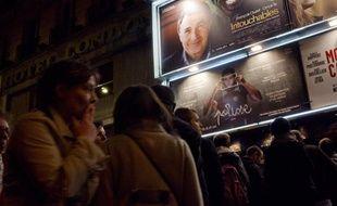 Des gens font la queue devant une salle de cinéma parisienne.