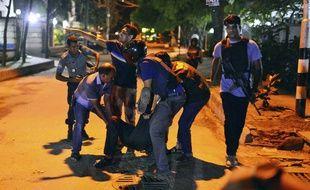 Des policiers évacuent un blessé lors de la prise d'otages dans un restaurant à Dacca, le 1er juillet.