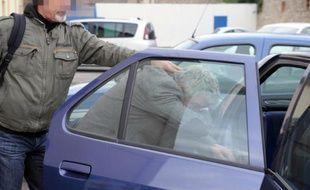 """La tête supposée du réseau de trafic de viande de cheval impropre à la consommation, Patrick Rochette et propriétaire de la """"Narbonnaise des viandes"""", rentre dans une voiture de police, le 16 décembre 2013 à Narbonne"""