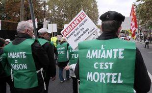 Des participants protestent contre l'amiante lors d'une manifestation, le 12 octobre 2013 à Paris, à l'appel de l'Association nationale de défense des victimes de l'amiante (Andeva)