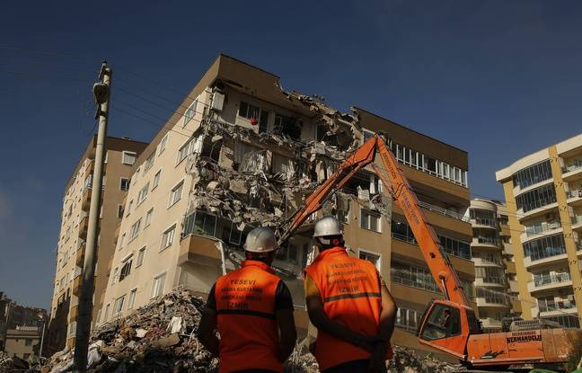 648x415 workers watch as colleague in a bulldozer works on demolishing a building that was damaged at the