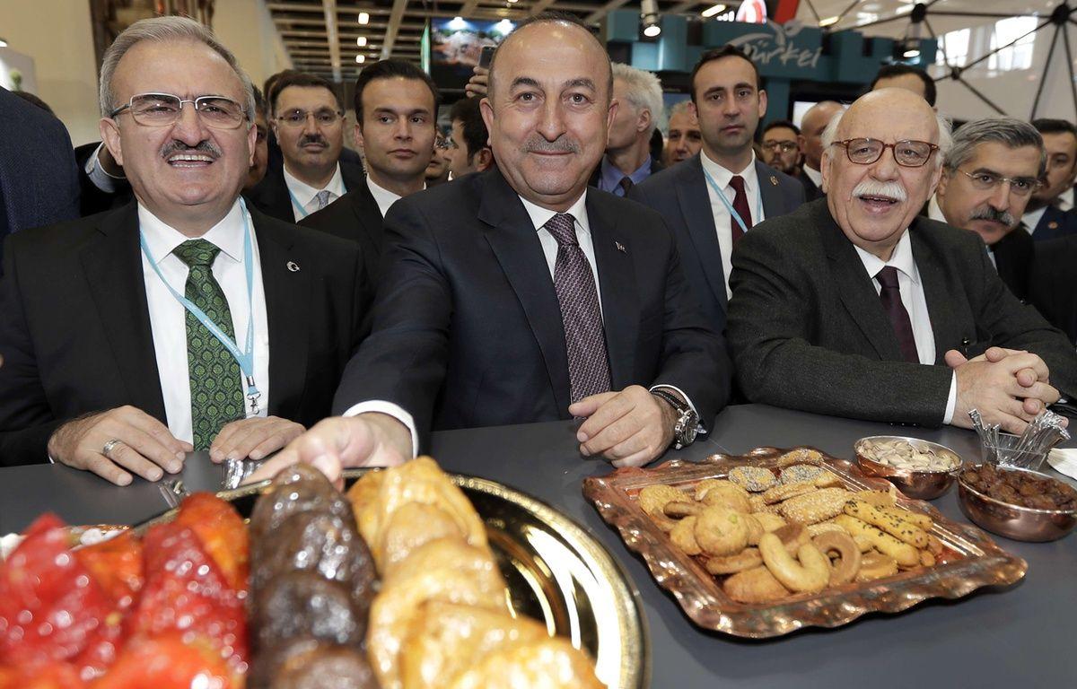 Mevlut Cavusoglu (au centre) propose des pâtisseries aux journalistes, mercredi 8 mars, à Berlin. – Michael Sohn/AP/SIPA