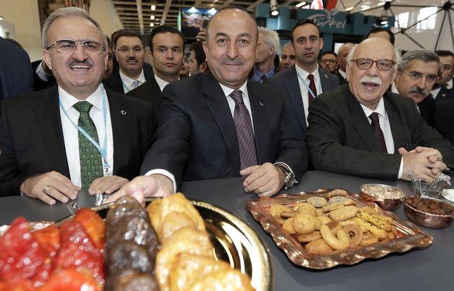 Mevlut Cavusoglu (au centre) propose des pâtisseries aux journalistes, mercredi 8 mars, à Berlin.