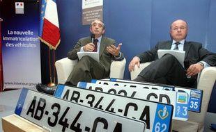 Yves Nossé, directeur du système d'immatriculation des véhicules et Gérard Gachet, porte-parole de la ministre de l'Intérieur, présentent  les nouvelles plaques d'immatriculation qui entrent en vigueur le 15 avril 2009.