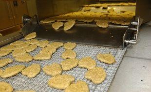 Des ouvriers supervisent la production de nuggets de poulet dans une usine de Saint-Cyr-en-Val près d'Orléans.