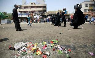 Des Irakiens passent à côté de fleurs et de chaussures laissées en hommage aux victimes d'un attentat à la voiture piégée, dans le quartier Sadr Area à Bagdad le 12 mai 2016