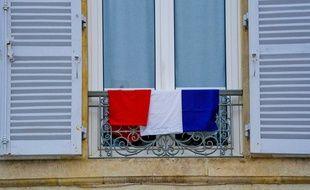 Illustration d'un drapeau français, accroché à une fenêtre.